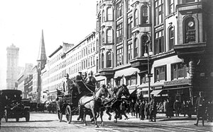 Horse-drawn fire engines in street, on their w...