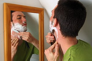 A man shaving with a cut-throat razor