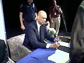 Homme assis à une table, signant des livres.
