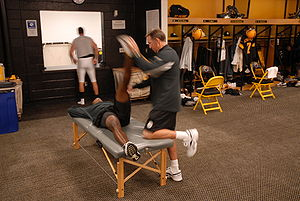 A coach stretches out a Pittsburgh Steeler pri...