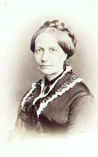 Head and shoulders sepia photograph showing a woman with dark hair and wearing a dark satin Victorian dress with lace around the collar