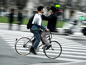 Two men riding one bicycle in Paris, France.