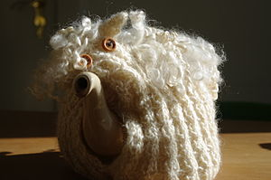English: tea pot with knitted tea cosy sheep