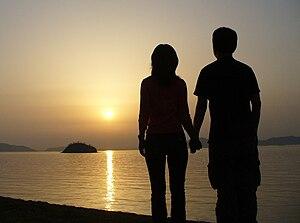 日本語: 夕日を眺める恋人(男女) English: A Japanese couple h...
