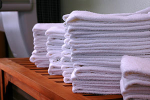 Several stacks of gym towels on a wooden bench.