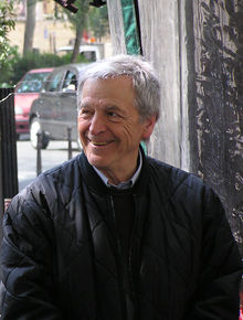 Photograph of the head and upper body of a smiling man looking well to the left of the camera. He is wearing a collared shirt and a pullover sweater underneath a jacket. He is apparently sitting, and well behind him there is a street with two cars visible.