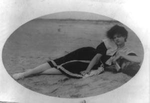 Woman in bathing suit lying on beach.
