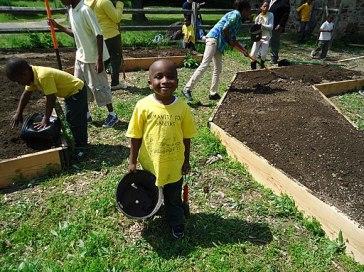 Children volunteers helping plant a pollinator garden