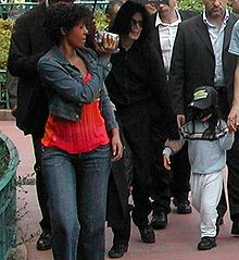 A group of adults and a child are shown in the photo. An African American female with short brown hair who is wearing a jean jacket and a light wash pair of jeans with a red shirt is seen holding a video camera, which is pointing forward. To the right of the female there is an opened black umbrella that is held above a light-skinned male with long black hair who is wearing all black clothes. In front of the male there is a child with black hair that is wearing a black cap with a blue shirt, a pair of white pants and black shoes. To the farthest right there are two Caucasian males with dark brown hair. In the background, trees, bushes and people can be seen.