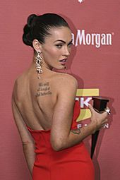 """Photograph showing Megan Fox's tattoo of the quote """"We will all laugh at gilded butterflies"""" and a partial view of her tattoo of Marilyn Monroe's face"""