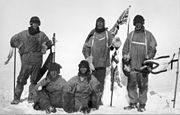 Five men(three standing, two sitting on the icy ground) in heavy polar clothing. All look exhausted and unhappy. The standing men are carrying flagstaffs and a Union flag flies from a mast in the background.Scott's party at the South Pole. Left to right: Wilson; Bowers; Evans; Scott; Oates