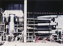 Tiny men and a large silver cylindrical object connected to a lot of scaffolding and tubes