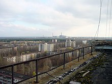 The abandoned city of Pripyat with Chernobyl plant in the distance
