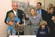 Netanyahu lighting Hanukkah candles on the first night in the Prime Minister's office in Jerusalem with his wife, Sara and their sons, Yair and Avner, 1996