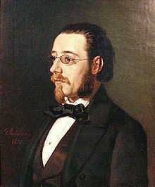 Portrait of a fairly young man in spectacles, with beard, moustache and longish hair, wearing a dress shirt with a large floppy bow tie