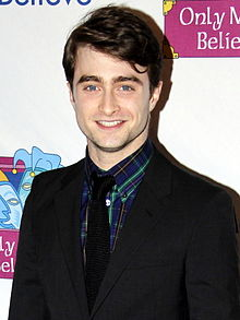 A male in his early twenties with brown hair and blue eyes is smiling at the camera.