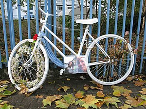 White bicycle chained to railings as a memoria...