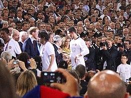 Un homme en chemise blanche reçoit la médaille d'un homme en costume.