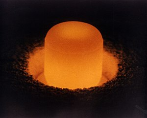 A pellet of plutonium-238, glowing under its o...