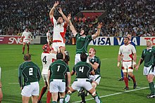 Two rows of opposing players, green to the fore, white behind, each aid a jumping player from their team by lifting him towards an off-picture ball travelling overhead.