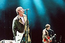 A color photograph of Noel and Liam Gallagher of the band Oasis on stage