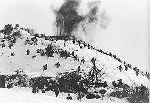 A snow covered hill with the hill top on fire and the slopes filled with charging soldiers