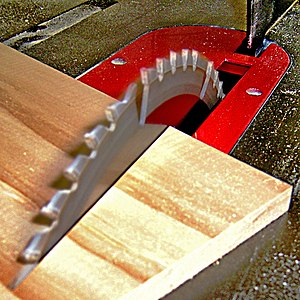 The spinning blade of a table saw cutting wood...