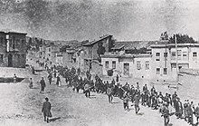 Une colonne de personnes encadrée par des hommes en armes à la sortie d'une ville