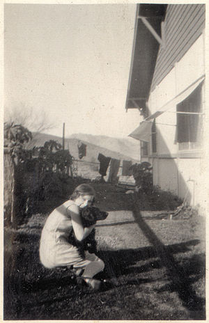 Girl hugging a dog in a house's side yard, Ari...