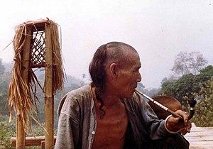Hombre akha fumando opio en pipa