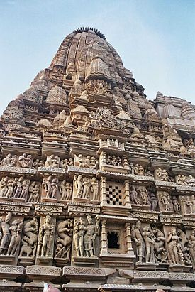 A typical temple at Khajuraho with divine couples. Note lace-like ornamentation on the major and the minor shikharas.