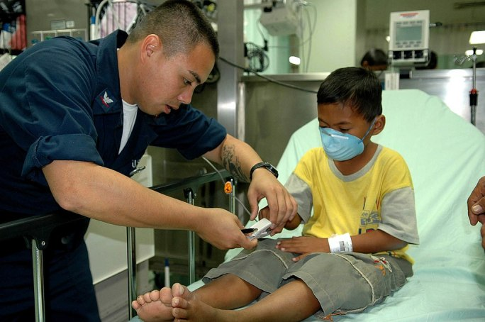 US Navy 060528-N-3714J-030 Navy Hospital Corpsman Lawrence Santos of Stockton, Calif., takes the pulse of a child aboard the Military Sealift Command (MSC) hospital ship USNS Mercy (T-AH 19)