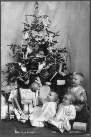 Three small children with Christmas tree and p...