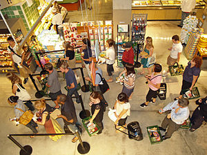 English: Customers waiting in line to check ou...