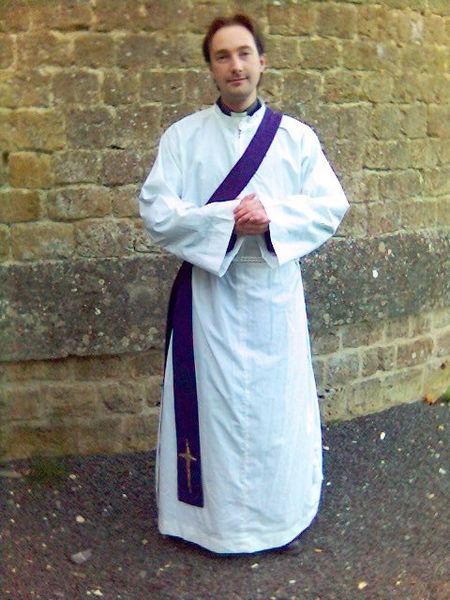 Anglican Priest wearing an alb, cincture, and purple Deacon's stole.