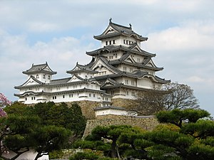 Photo of the central castle towers in the Himeji Castle complex, projected against the blue sky. Trees can be seen in the grounds below the castle towers.