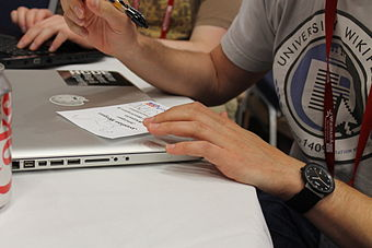 Jonathan Morgan draws a dinosaur on his badge during Wikimania 2012.