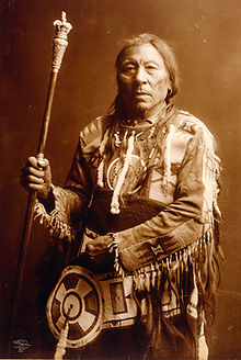 A sepia photograph of Aatsista-Mahkan (Running Rabbit). He is wearing what is usually described as a buckskin outfit. It is elaborate and he is holding a pole.