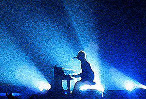 Chris Martin of Coldplay playing piano at a co...