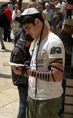 English: A man at the Western Wall wearing bot...