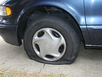 A flat tire on a Mercury Villager van.