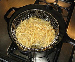 A cast iron chip pan with an aluminum basket b...