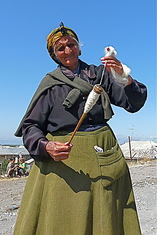 An photo of an older woman holding a drop spindle with yarn wrapped around it in her right hand, in her left hand is a ball of wool which she is spinning.