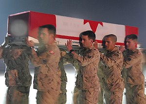 Canadian soldiers carry the coffin of a fallen...