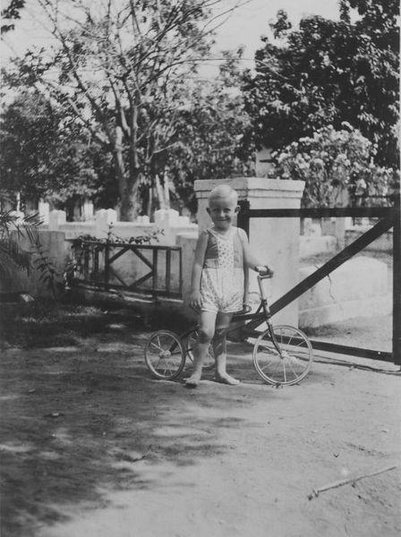 448px COLLECTIE TROPENMUSEUM Europese jongen poseert met zijn driewieler bij het hek in de tuin van zijn huis TMnr 60044639 Mainan Bocah Belanda VS Mainan Bocah Pribumi