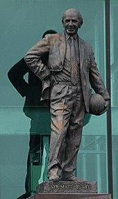 A statute of Sir Matt Busby holding a ball