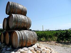 Oak wine barrels stacked upon galet rocks in a...