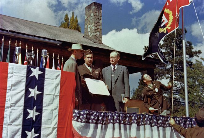 """Presentation of the Army-Navy """"E"""" Award at Los Alamos on October 16, 1945. Oppenheimer (left) gave his farewell speech as director on this occasion. Robert Gordon Sproul right, in suit, accepted the award on behalf of the University of California from Leslie Groves (center).[92]"""