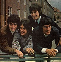 Four smiling young men leaning over the back of a green park bench, a row of three-story-tall residential buildings behind them. The man on the left wears a brown sports jacket and white turtleneck; the man to his right wears a black-and-white-striped pullover shirt; the man to his right (standing straighter, just behind the other three) wears a black suit and tie; the man on the far right wears a black sports jacket and white shirt.