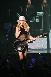 A blond woman standing on a stage. She has curvy, flowing hair and is dressed in a black, translucent top with boots in her leg and a white hat. The woman is holding an electric guitar with her left hand and singing in to a microphone in her right. She is surrounded by audience members whose heads can be seen in the image. Behind the woman, tow back-up singers can be seen in the distance.